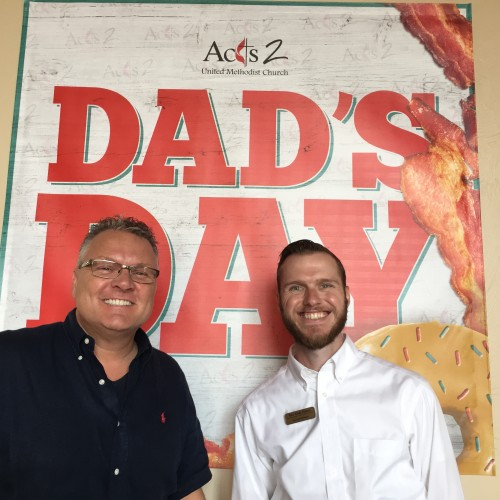 Mark and Andy standing in front of the Dad's Day banner